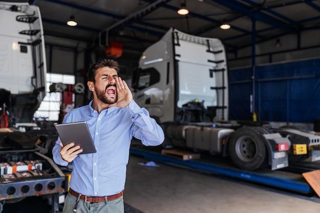 若いひげを生やした輸出部門の責任者がガレージに立ち、タブレットを持って従業員に電話をかけました。