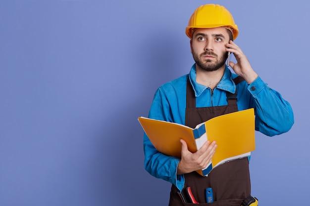 若いひげを生やした建設労働者茶色のエプロン、電話、ビジネス会話、深刻な表情のウィットパートナーの話。