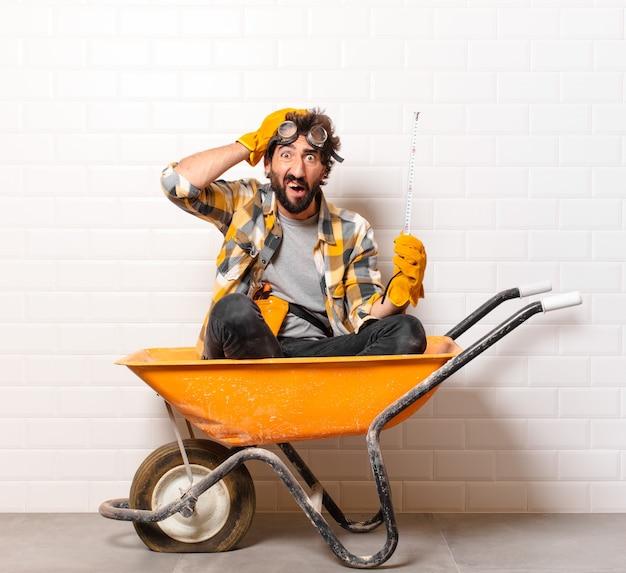 Молодой бородатый строитель человек на тачке