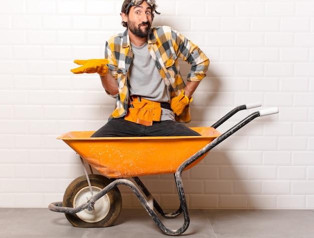 젊은 수염 된 수레에 건설 노동자 남자