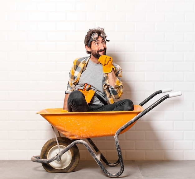 手押し車の若いひげを生やした建設労働者の男