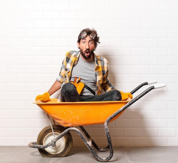 手押し車に若いひげを生やした建設労働者男