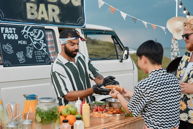 Young bearded cook preparing sandwiches for young people outdoors