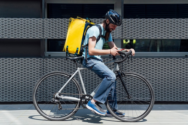 Young bearded courier delivering food on a bicycle, checking order with a smart phone .delivery service concept