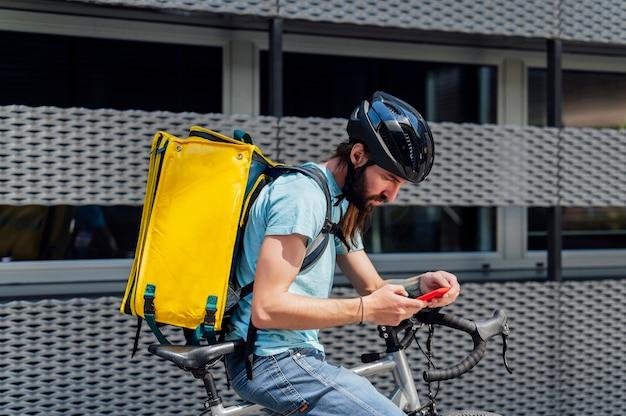 Молодой бородатый курьер доставляет еду на велосипеде, проверяя заказ с помощью смартфона. концепция службы доставки