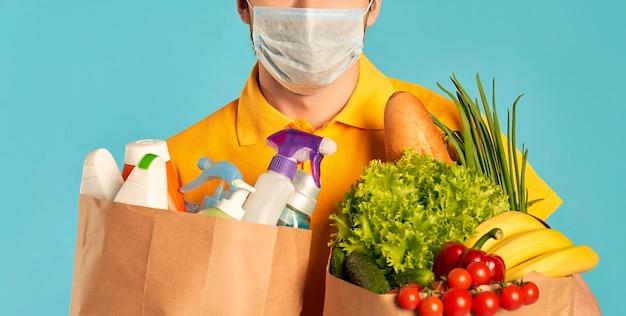 Молодой бородатый курьер-курьер в защитной маске с бумажным пакетом продуктов питания и бытовой химии, косметики изолированы. доставка на дом.
