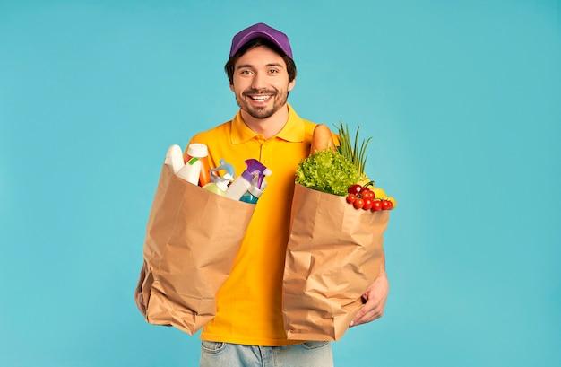 Молодой бородатый курьер курьерской доставки в униформе с бумажным пакетом продуктов питания и бытовой химии, косметики изолированы. доставка на дом.