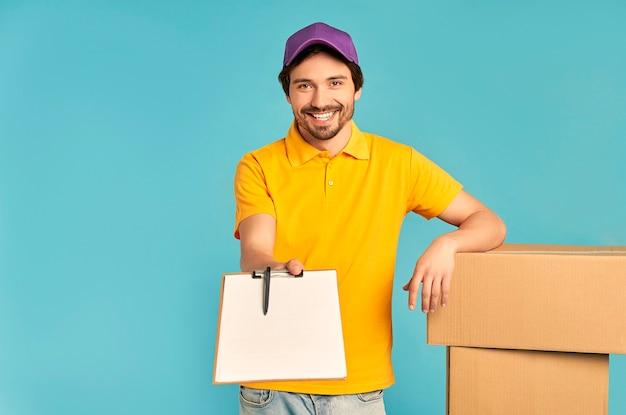 Молодой бородатый курьер-доставщик в униформе с коробками протягивает изолированный документ для подписи. доставка на дом.