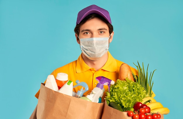 Young bearded courier delivery man in a protective mask with a paper package of food and household chemicals, cosmetics isolated. home delivery.