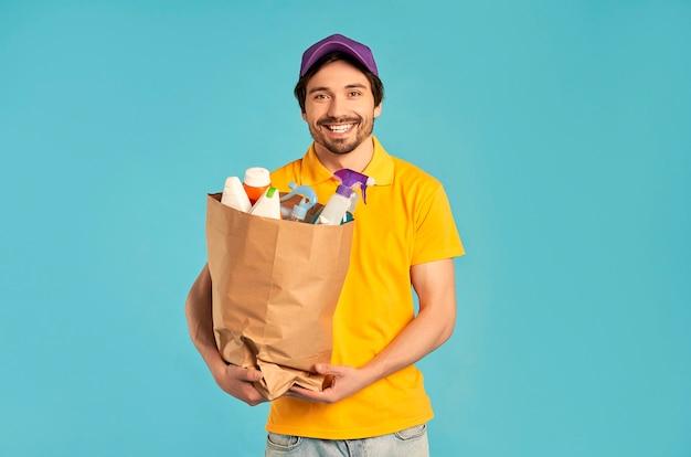 Молодой бородатый курьер-доставщик с бумажным пакетом бытовой химии, изолированной косметики. доставка на дом.