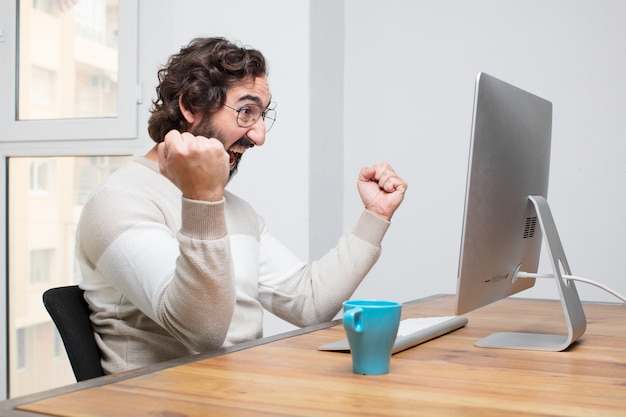 Young bearded crazy freelancer working with his computer