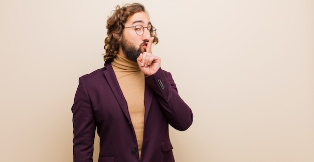 Young bearded crazy man asking for silence and quiet, gesturing with finger in front of mouth, saying shh or keeping a secret against flat color wall