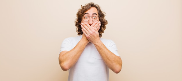 Young bearded crazy man covering mouth with hands with a shocked, surprised expression, keeping a secret or saying oops
