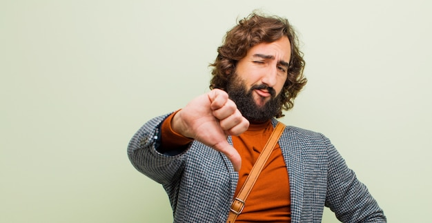 Young bearded crazy man feeling cross, angry, annoyed, disappointed or displeased, showing thumbs down with a serious look against flat color