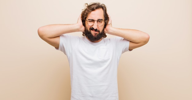 Young bearded crazy man feeling frustrated and annoyed, sick and tired of failure, fed-up with dull, boring tasks against flat color wall