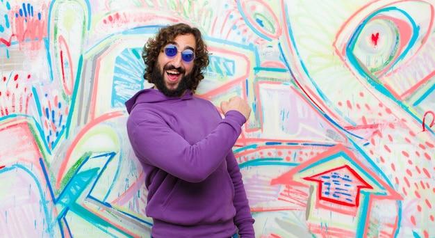 Молодой бородатый сумасшедший, чувствуя себя счастливым, позитивным и успешным, мотивированным, когда сталкивается с проблемой или празднует хорошие результаты на фоне граффити