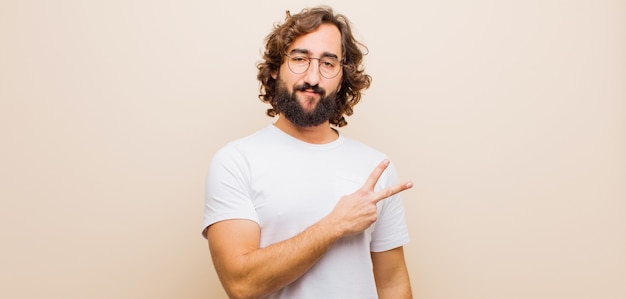 Young bearded crazy man feeling happy, positive and successful, with hand making v shape over chest, showing victory or peace against flat color wall