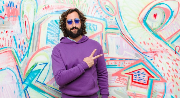 Young bearded crazy man feeling happy, positive and successful, with hand making v shape over chest, showing victory or peace on graffiti wall