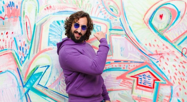 Young bearded crazy man feeling happy, satisfied and powerful, flexing fit and muscular biceps, looking strong after the gym on graffiti wall
