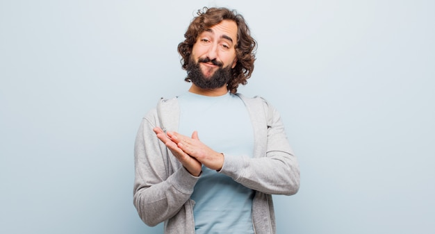 Young bearded crazy man feeling happy and successful, smiling and clapping hands, saying congratulations with an applause against flat color wall