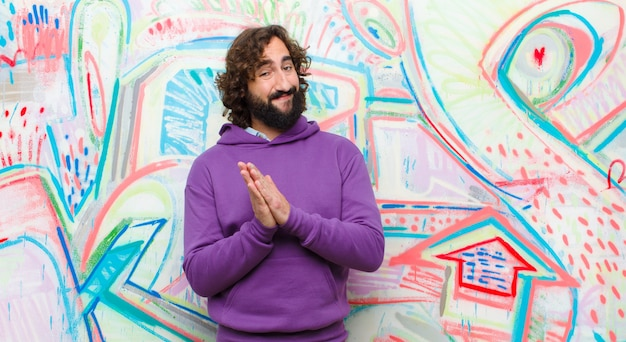 Young bearded crazy man feeling happy and successful, smiling and clapping hands, saying congratulations with an applause against graffiti wall
