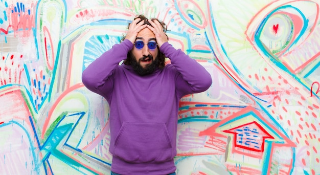 Young bearded crazy man feeling horrified and shocked, raising hands to head and panicking at a mistake against graffiti wall