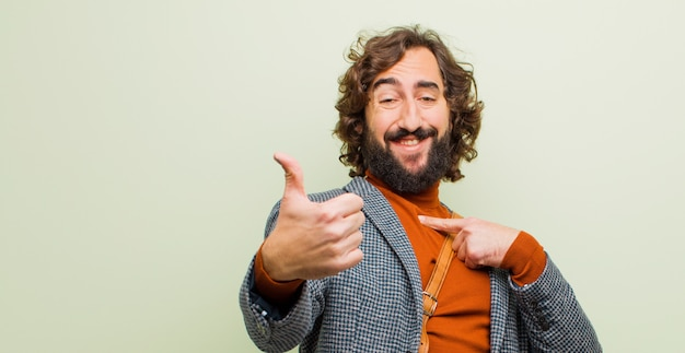 Young bearded crazy man feeling proud, carefree, confident and happy, smiling positively with thumbs up against flat color