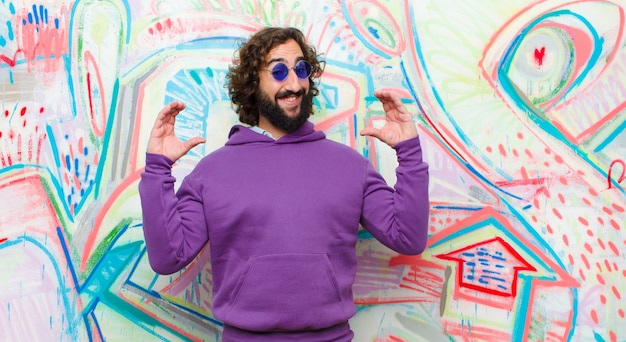Young bearded crazy man framing or outlining own smile with both hands, looking positive and happy, wellness concept against graffiti