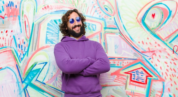 Young bearded crazy man laughing happily with arms crossed, with a relaxed, positive and satisfied pose on graffiti wall