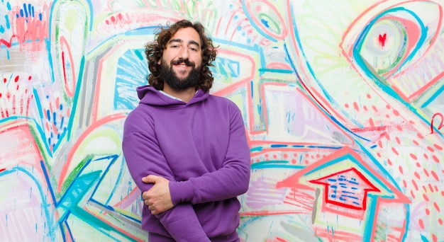 Young bearded crazy man laughing shyly and cheerfully, with a friendly and positive but insecure attitude against graffiti wall