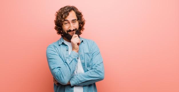 Молодой бородатый сумасшедший смотрит счастливым и улыбается рукой на подбородке, задается вопросом или задает вопрос, сравнивая варианты с плоским цветом