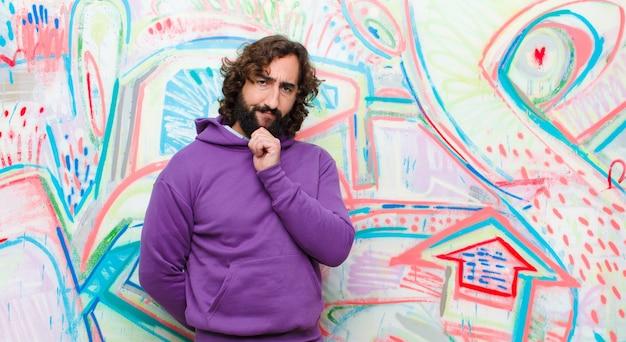 Молодой бородатый сумасшедший смотрит счастливым и улыбается рукой на подбородке, задается вопросом или задает вопрос, сравнивая варианты с граффити стеной