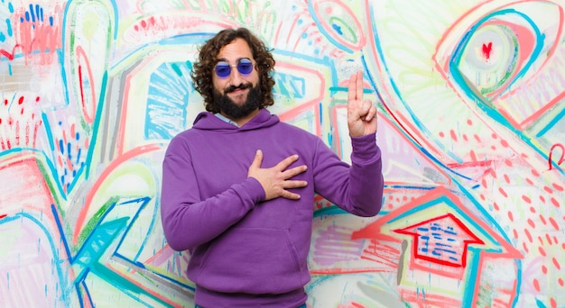 Young bearded crazy man looking happy, confident and trustworthy, smiling and showing victory sign, with a positive attitude against graffiti