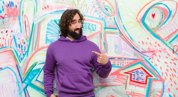 Young bearded crazy man looking proud, arrogant, happy, surprised and satisfied, pointing to self, feeling like a winner against graffiti