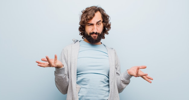 Young bearded crazy man looking puzzled, confused and stressed, wondering between different options, feeling uncertain against flat color wall