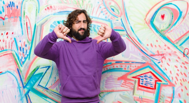 Young bearded crazy man looking sad, disappointed or angry, showing thumbs down in disagreement, feeling frustrated against graffiti wall