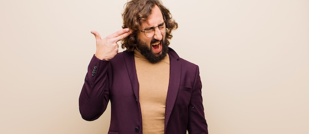 Young bearded crazy man looking unhappy and stressed, suicide gesture making gun sign with hand, pointing to head against flat color wall
