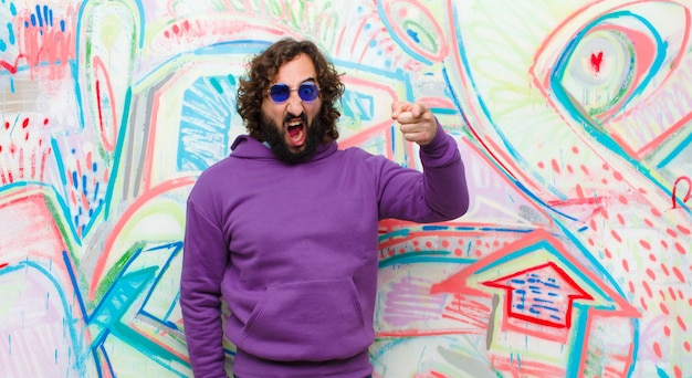 Young bearded crazy man pointing at camera with an angry aggressive expression looking like a furious, crazy boss against graffiti wall