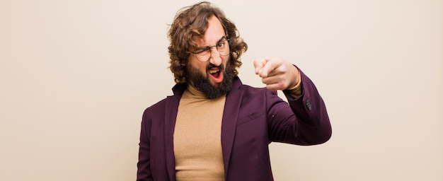 Young bearded crazy man pointing at camera with an angry aggressive expression looking like a furious, crazy boss