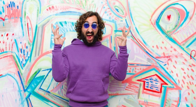 Young bearded crazy man screaming with hands up in the air, feeling furious, frustrated, stressed and upset against graffiti wall