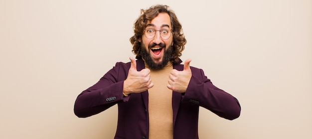 Young bearded crazy man smiling broadly looking happy, positive, confident and successful, with both thumbs up against pink wall