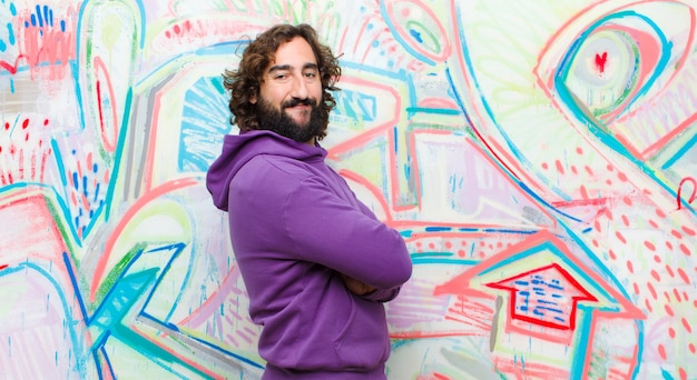 Young bearded crazy man smiling to camera with crossed arms and a happy, confident, satisfied expression, lateral view on graffiti wall
