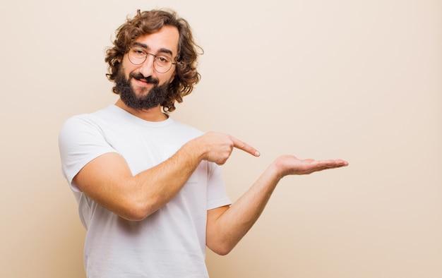 Молодой бородатый сумасшедший, весело улыбаясь и указывая на copyspace на ладони на стороне, показывая или рекламируя объект против плоского цвета