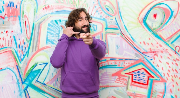 Young bearded crazy man smiling cheerfully and pointing to camera while making a call you later gesture, talking on phone on graffiti wall