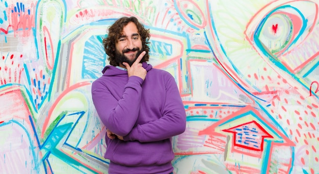Young bearded crazy man smiling, enjoying life, feeling happy, friendly, satisfied and carefree with hand on chin on graffiti wall