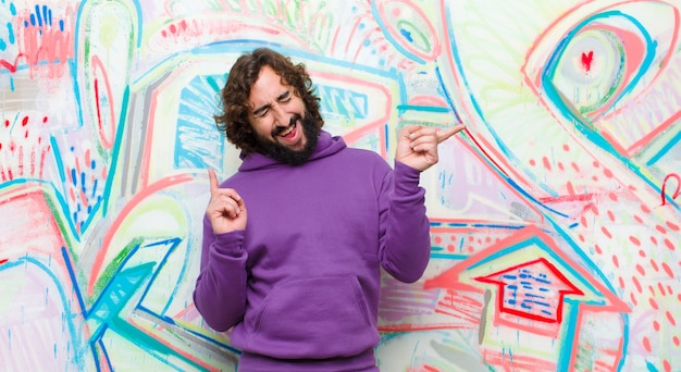 Young bearded crazy man smiling, feeling carefree, relaxed and happy, dancing and listening to music, having fun at a party against graffiti