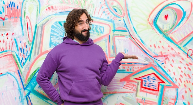 Young bearded crazy man smiling, feeling confident, successful and happy, showing concept or idea on copy space on the side on graffiti wall