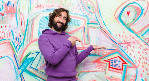 Young bearded crazy man smiling, feeling happy, carefree and satisfied, pointing to concept or idea on copy space on the side on graffiti wall