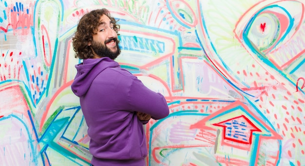 Young bearded crazy man smiling gleefully, feeling happy, satisfied and relaxed, with crossed arms and looking to the side against graffiti