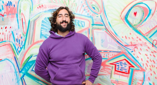 Young bearded crazy man smiling happily with a hand on hip and confident, positive, proud and friendly attitude against graffiti wall